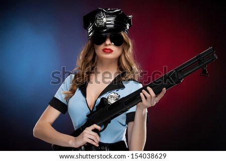 Sexy policewoman. Beautiful young policewoman in uniform holding gun while standing isolated on colored background - stock photo