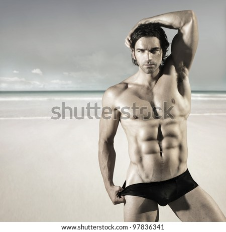 Sexy portrait of a hot buff male fitness model pulling at his bikini briefs on the beach - stock photo