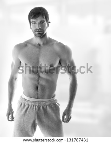 Sexy portrait of a very muscular hot shirtless male model in in sweatpants with copy space - stock photo