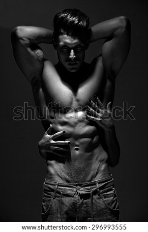 Sexy portrait of a very muscular male model in sensual pose. - stock photo