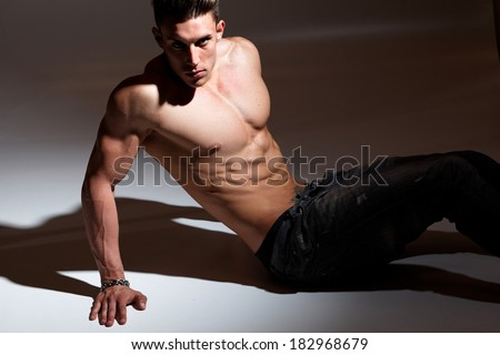 Sexy portrait of a very muscular shirtless male model against grey wall in sensual pose  - stock photo