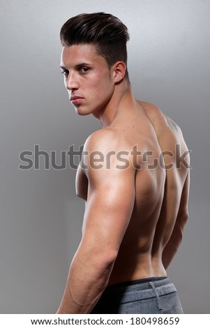 Sexy portrait of a very muscular shirtless male model against grey wall in sensual pose . Fashion colors.  - stock photo