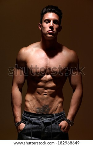 Sexy portrait of a very muscular shirtless male model against grey wall in sensual pose .Low light. Shallow depth of field with focus on abdominals.