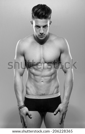 Sexy portrait of a very muscular shirtless male model against white wall in sensual pose. B&W - stock photo