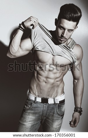 Sexy portrait of a very muscular shirtless male model against white wall in sensual pose . Glamour color  - stock photo