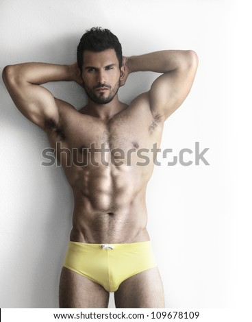 Sexy portrait of a very muscular shirtless male model in underwear against white wall in sensual pose