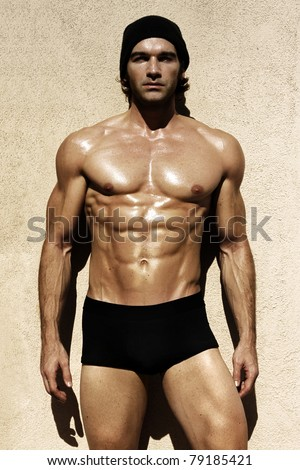 Sexy portrait of a very muscular shirtless male model looking away - stock photo