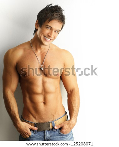 Sexy portrait of a young muscular male model with great happy smile against white wall - stock photo