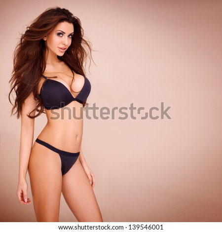Sexy pose of a dark haired woman wearing a black bikini - stock photo