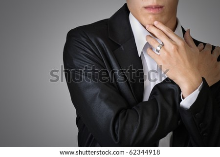 Sexy pose of business man over studio gray background.