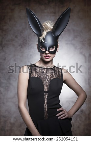 Sexy, pretty, elegant blonde woaman in carnival rabbit mask, balck dress and make up. - stock photo