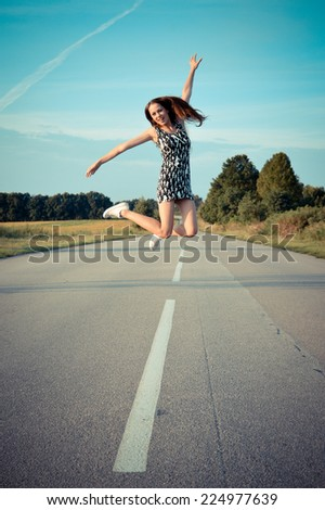 sexy pretty girl in mini dress jumping high and happy smiling on blue sky outdoors copy space background portrait - stock photo