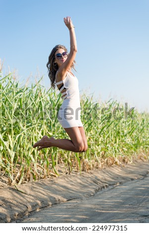 sexy pretty girl in white mini dress jumping high and happy smiling on blue sky outdoors copy space background portrait - stock photo