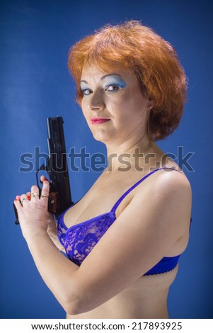 sexy red-haired middle-aged woman with a gun wearing a blue bra on a blue background - stock photo