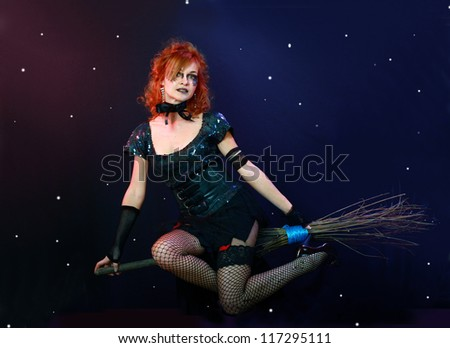 Sexy red haired witch flying on broom on a dark sky with stars - stock photo