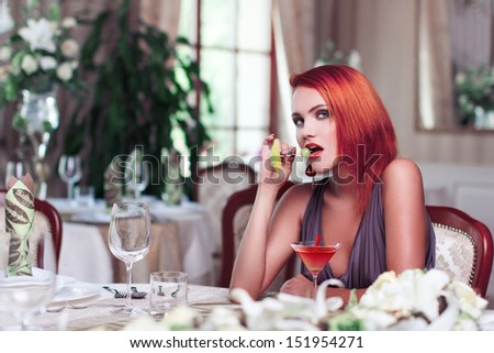 Sexy redhead woman with drink, seduction - stock photo