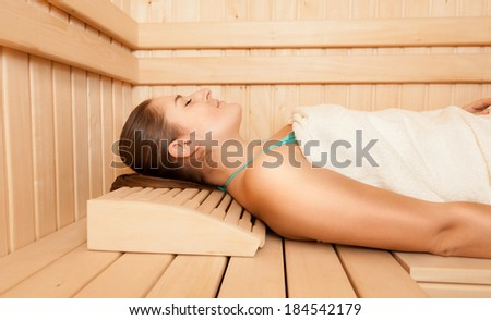 Sexy relaxed woman lying on bench at sauna