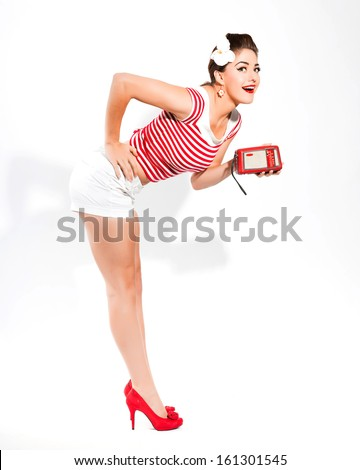 Sexy retro pin-up girl with radio and red lipstick wearing red striped shirt and white hot pants. Standing against white wall. - stock photo