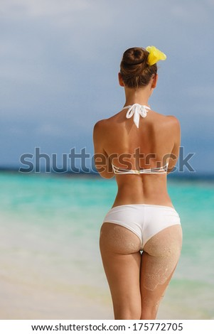 Sexy sandy woman buttocks on tropical beach background near ocean - stock photo