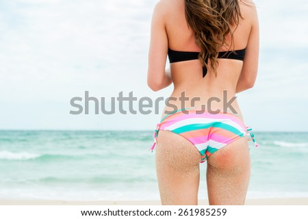 Sexy sandy woman buttocks on tropical beach background near ocean  - stock photo