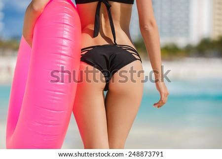 Sexy sandy woman buttocks on tropical beach background near ocean.  close up outdoor shot of young woman in white bikini, sunbathing at sea shore. Black bikini - stock photo