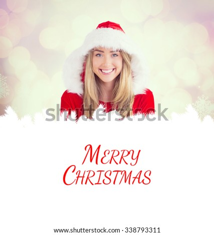 Sexy santa girl holding gift against glowing christmas background - stock photo
