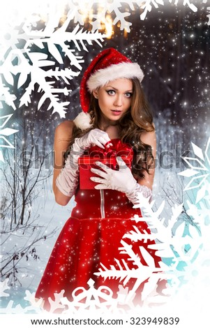 Sexy santa girl holds gift box on the snowflakes pattern  - stock photo