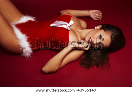Sexy santa helper lie on red background - stock photo