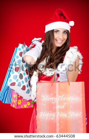 sexy santa woman holding colorful shopping bags - stock photo