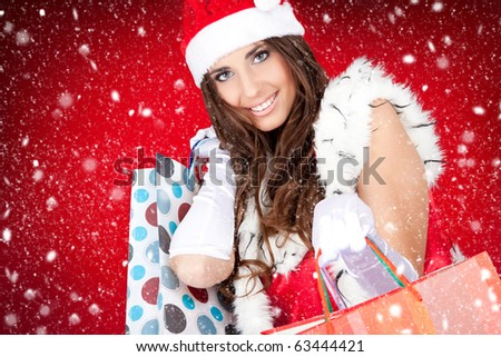 sexy santa woman holding colorful shopping bags while snowing - stock photo