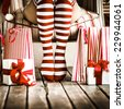 Sexy Santa woman legs. Christmas shopping concept. Xmas gift box - stock photo
