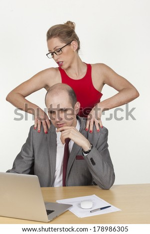 Sexy secretary making a massage to her boss while he is working on the laptop