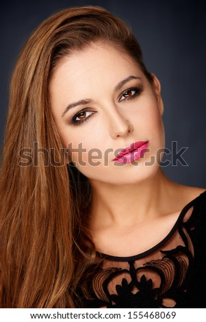Sexy seductive woman with long brunette hair and red lipstick looking sideways at the camera with a sultry look over a dark studio background - stock photo
