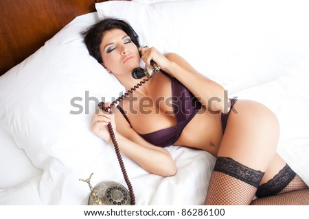 Sexy sensual woman making an erotic call in bed - stock photo
