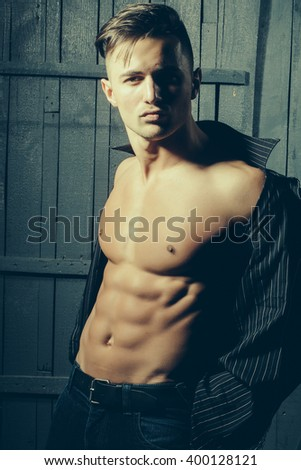 Sexy serious sensual muscular young macho man with bare torso and wet hair in shirt standing indoor on wooden background, vertical picture - stock photo