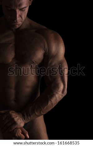 Sexy shirtless bodybuilder isolated on black background. Extreme strength, muscles and fitness. - stock photo