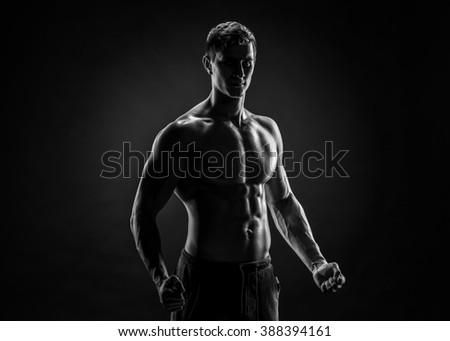 Sexy shirtless bodybuilder posing, looking at camera on black ba