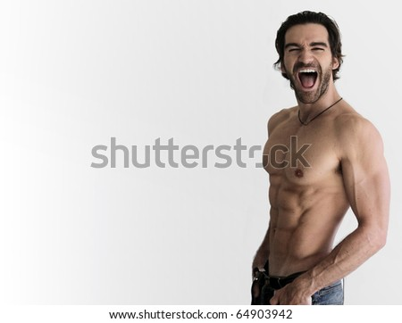 Sexy shirtless guy laughing against neutral background with lots of copy space - stock photo