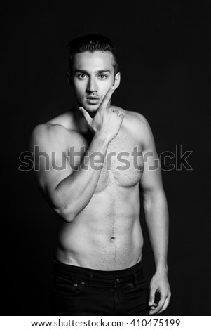 Sexy shirtless male model flirting against black background