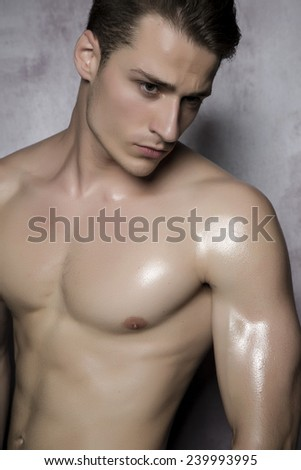 Sexy shirtless male model flirting against of grunge wall. - stock photo