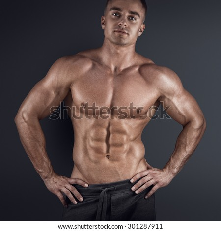 Sexy shirtless male model posing against dark background - stock photo