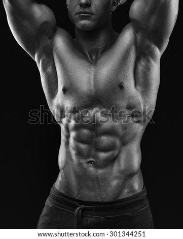 Sexy shirtless male model young bodybuilder posing over black background. Studio shot on black background. Black and white photo. - stock photo