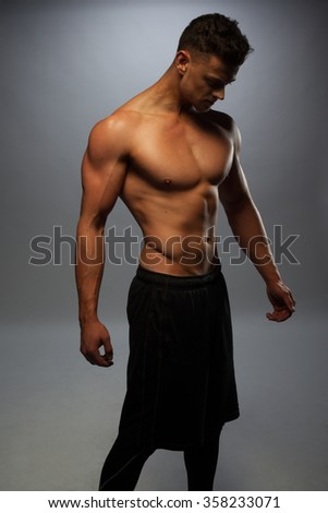 Sexy shirtless male model young bodybuilder posing over gray background. Studio shot standing on the side - stock photo