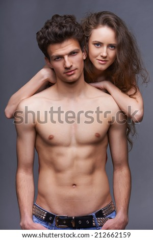 Sexy shirtless young couple embracing over gray background - stock photo