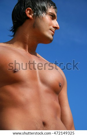 Sexy shirtless young man on the beach