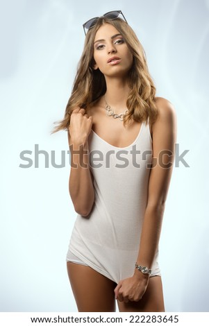 sexy shoot of young female in sensual pose with white comfortable undershirt, panties, sunglasse and necklace. Long hair, wellness body  - stock photo