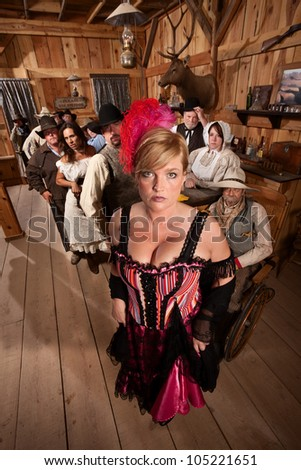 Sexy show girl shows off with large crowd in old west saloon - stock photo