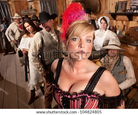 Sexy show girl with serious crowd in old west saloon - stock photo