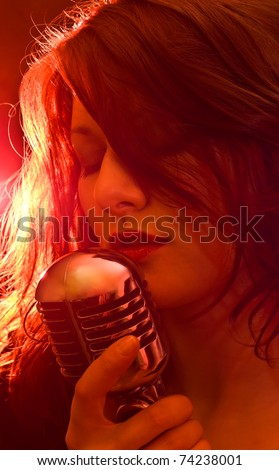 Sexy singer with retro microphone in strobe light