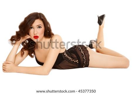 Sexy slim girl in black lingerie lying on white background - stock photo